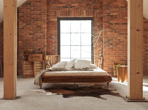 Do sypialni ze ścianą w cegle najlepiej komponuje sie naturalne drewno oraz betonowe szarości.  Cegła wprowadzi do wnętrza loftowego charakteru
