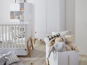 Lotta Bellamy. Pokój dziecka w stylu skandynawskim. Połączenie bieli z drewnem dębowym. Łóżeczko białe Lotta, szafa Lotta i skrzynia samochodzik na zabawki