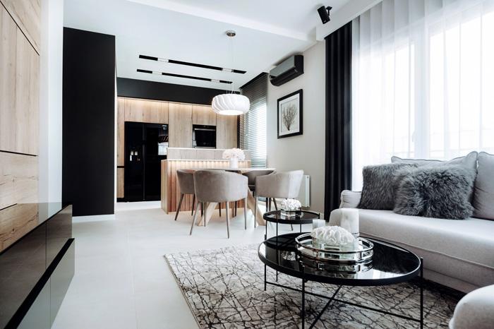 nowoczesny salon w niewielkim mieszkaniu połączenie czarni i drewna.