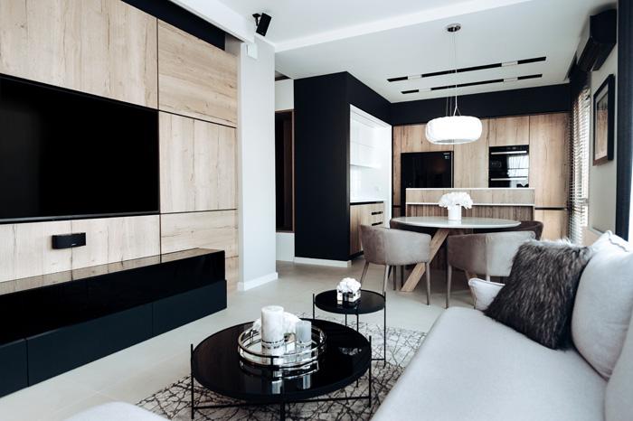 Modny i nowoczesny salon w 50 metrowym mieszkaniu. Salon w kolorach czerni, szarości i naturalnego drewna. Wzbogacony o szklane dodatki takie jak nowoczesne stoliki Cupid Zuiver